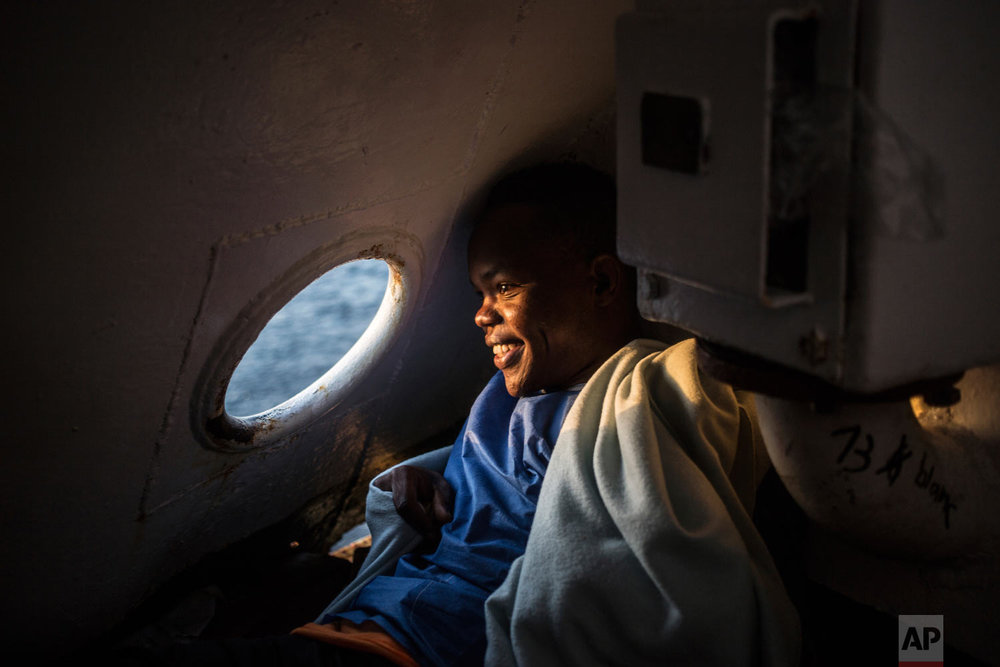 In this photo taken Thursday, Aug. 9, 2018, a migrant looks out of a porthole of the Open Arms boat, after being rescued off the coast of Libya in the early hours of the nigh of Thursday, Aug. 2, 2018. (AP Photo/Valerio Nicolosi)