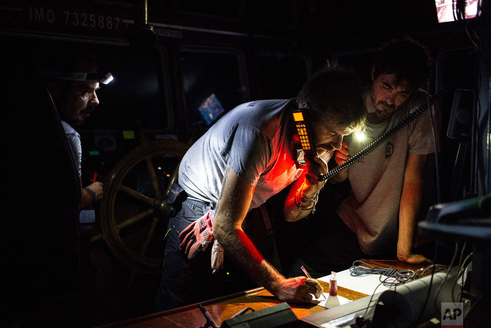 In this photo taken late Wednesday night, Aug. 1, 2018, Riccardo Gatti, rescue missions coordinator of the Open Arms boat, talks on the phone with the Libyan coast guard to coordinate a nighttime rescue operation off the coast of Libya. (AP Photo/Valerio Nicolosi)