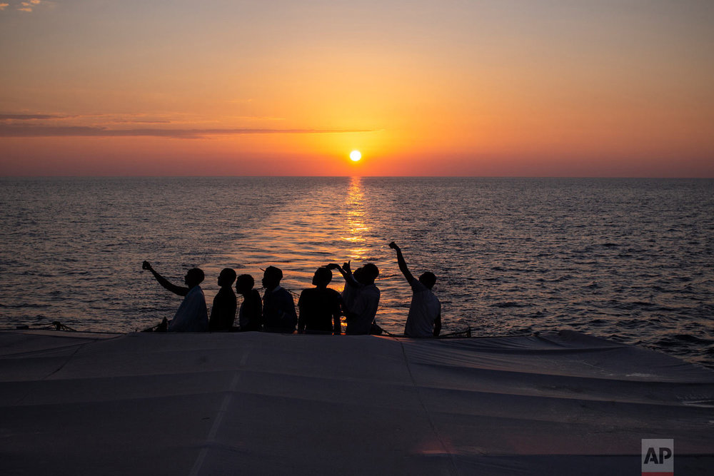 In this photo taken Saturday, Aug. 4, 2018, migrants stand on the deck of the Open Arms boat, after being rescued off the coast of Libya in the early hours of Thursday, Aug. 2, 2018.  (AP Photo/Valerio Nicolosi)