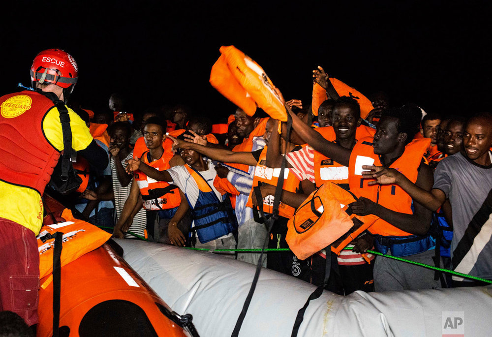 FILE -- In this photo taken in the early hours of Thursday night, Aug. 2, 2018 migrants wait to be rescued off the coast of Libya, as rescuers throw life jackets at them and urge them to stay calm. (AP Photo/Valerio Nicolosi)