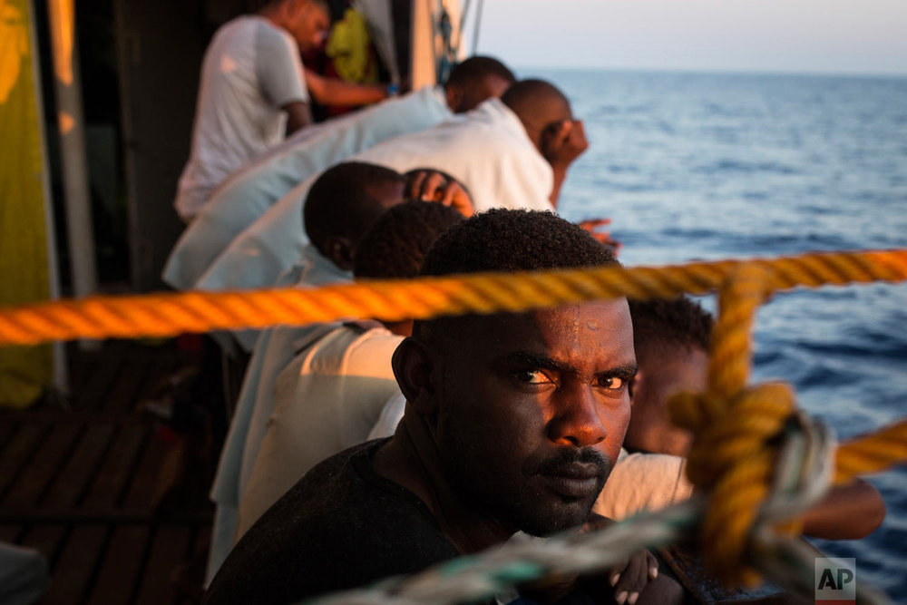 In this photo taken Friday, Aug. 3, 2018, migrants stand on the deck of the Open Arms boat, after being rescued off the coast of Libya in the early hours of the nigh of Thursday, Aug. 2, 2018. (AP Photo/Valerio Nicolosi)