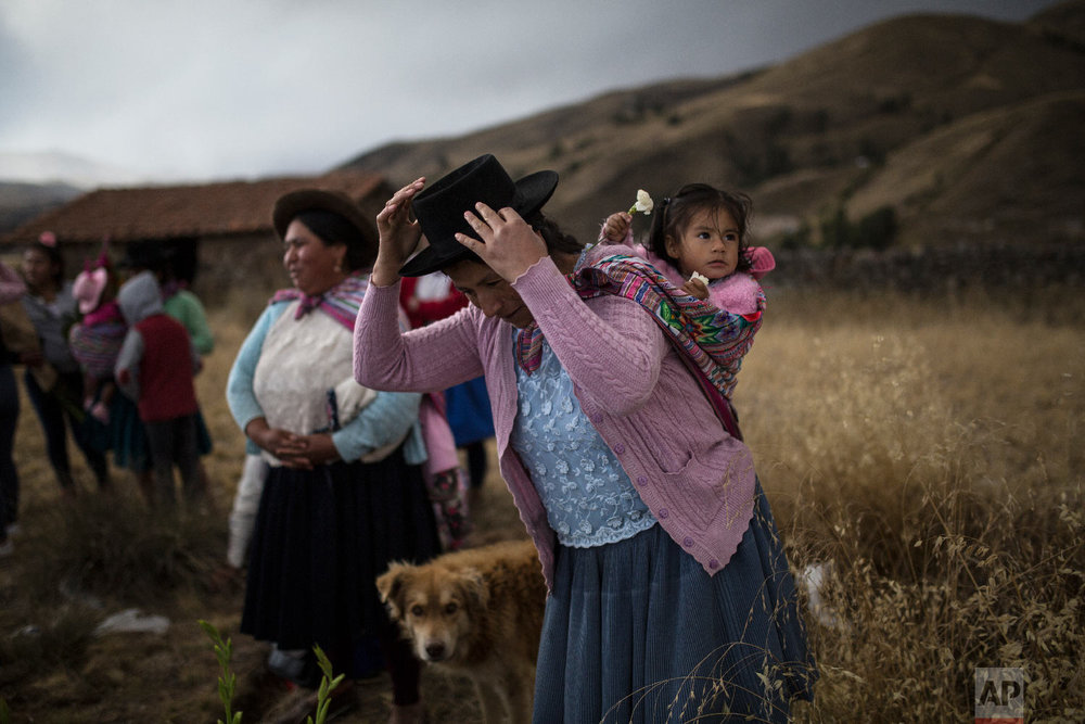 In this Aug. 14, 2018 photo, a woman carrying her daughter prepares to place flowers on the graves of relatives who were killed by the Peruvian army in 1983, during their proper burial at the Rosaspata cemetery, in Peru's Ayacucho province. (AP Photo/Rodrigo Abd)