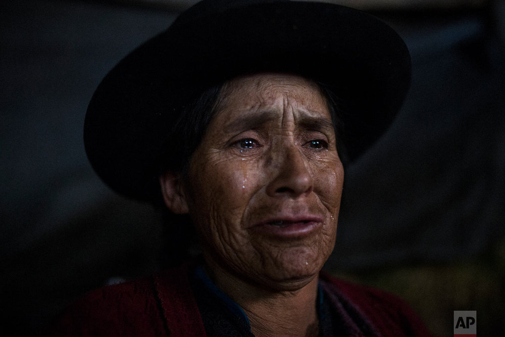 In this Aug. 15, 2018 photo, Antonia Yupanki Tineo, 58, cries near the coffin of her uncle Alejandro Tineo, who was killed by Shining Path guerrillas in 1984, as she attends his proper burial in Quinuas, in Peru's Ayacucho province. (AP Photo/Rodrigo Abd)