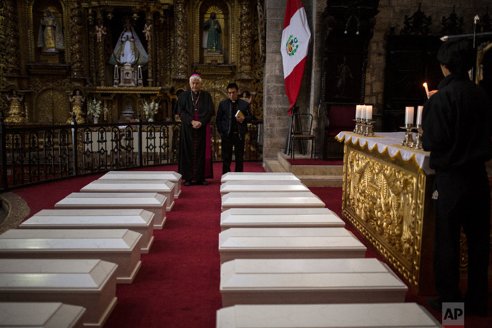 In this Aug. 14, 2018 photo, Ayacucho's Bishop Salvador Jose Miguel Pineiro, left, stands with an assistant behind the coffins of villagers who were killed by Shining Path guerrillas and the Peruvian army in the 1980s, inside the Cathedral in Ayacucho, Peru. (AP Photo/Rodrigo Abd)
