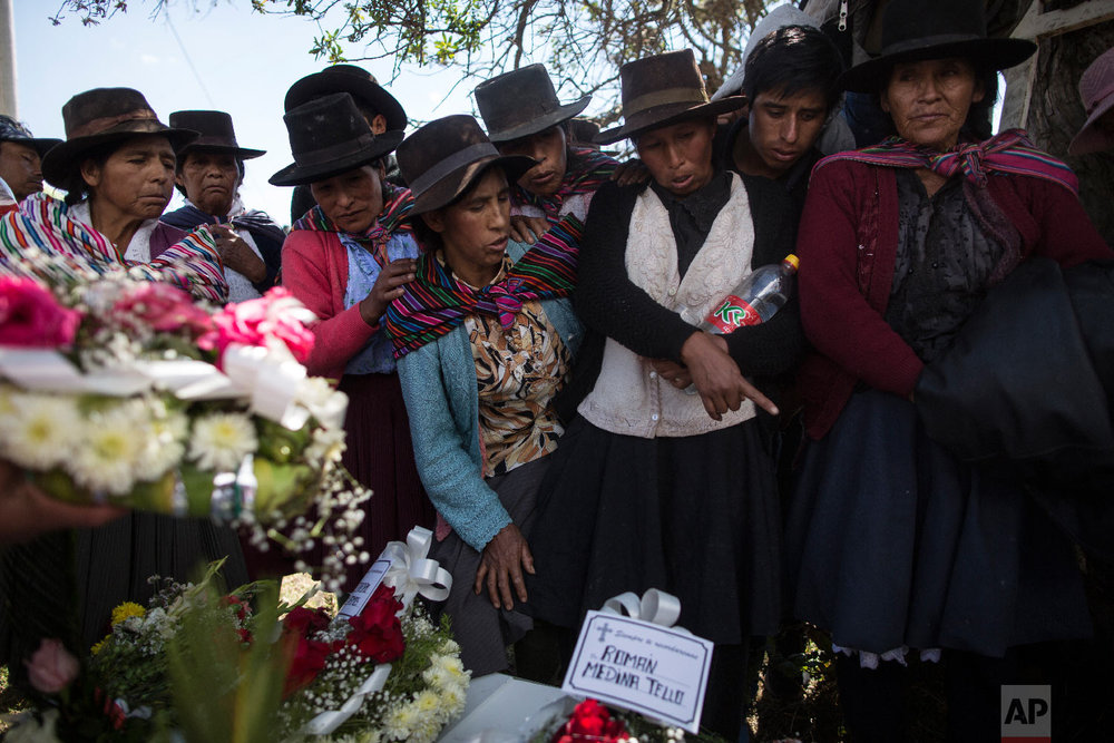 In this Aug. 15, 2018 photo, the relatives of people killed by Shining Path guerrillas and the Peruvian army in the 1980s look at the remains of their loved ones before their burial at the cemetery in Quinuas, in Peru's Ayacucho province. (AP Photo/Rodrigo Abd)