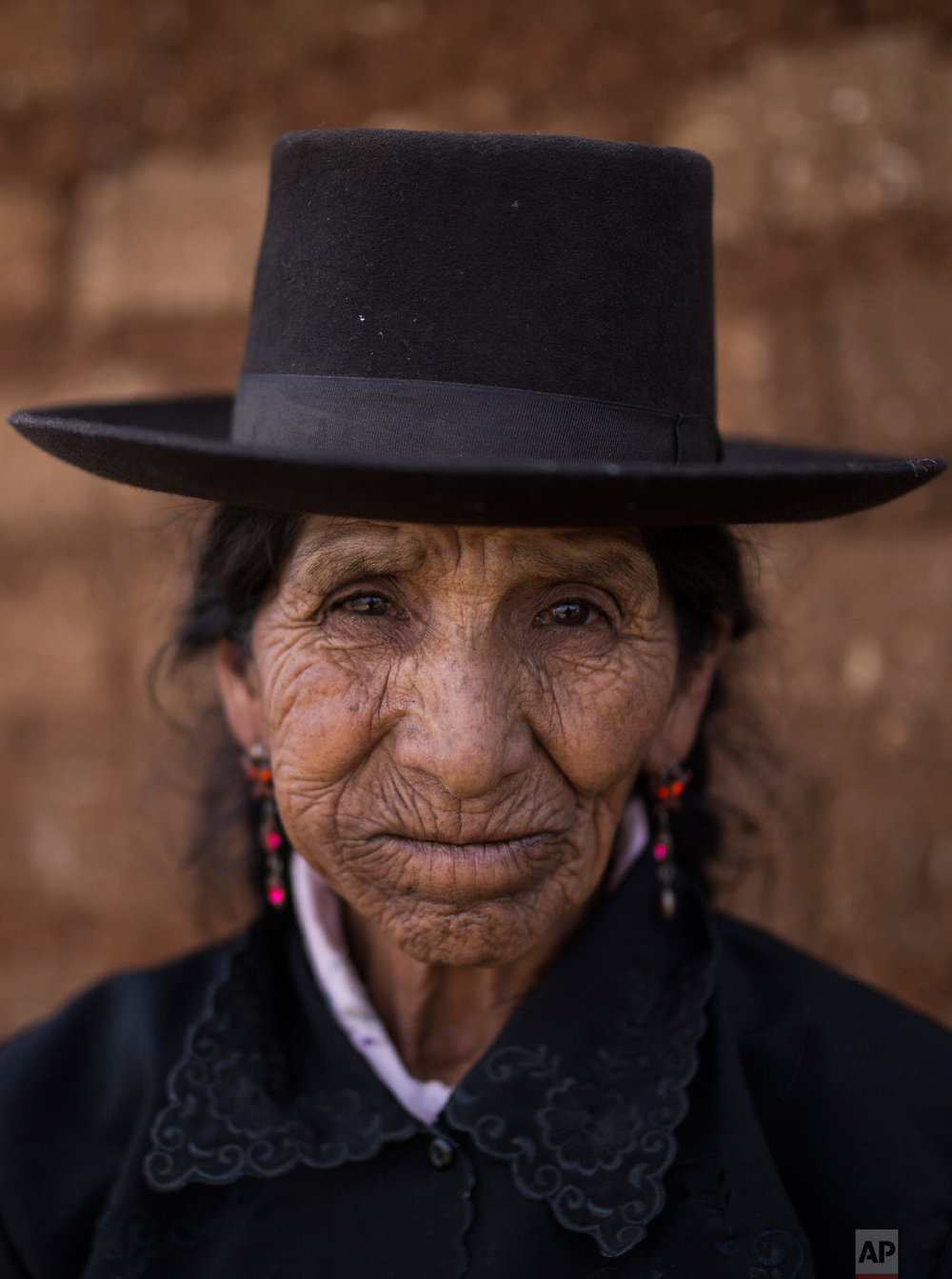 In this Aug. 15, 2018 photo, Maria Magdalena Espinosa, whose husband Daniel Tineo was  killed by the Shining Path guerrillas in 1984, poses for a portrait outside her home in Tantana, in Peru's Ayacucho province. (AP Photo/Rodrigo Abd)