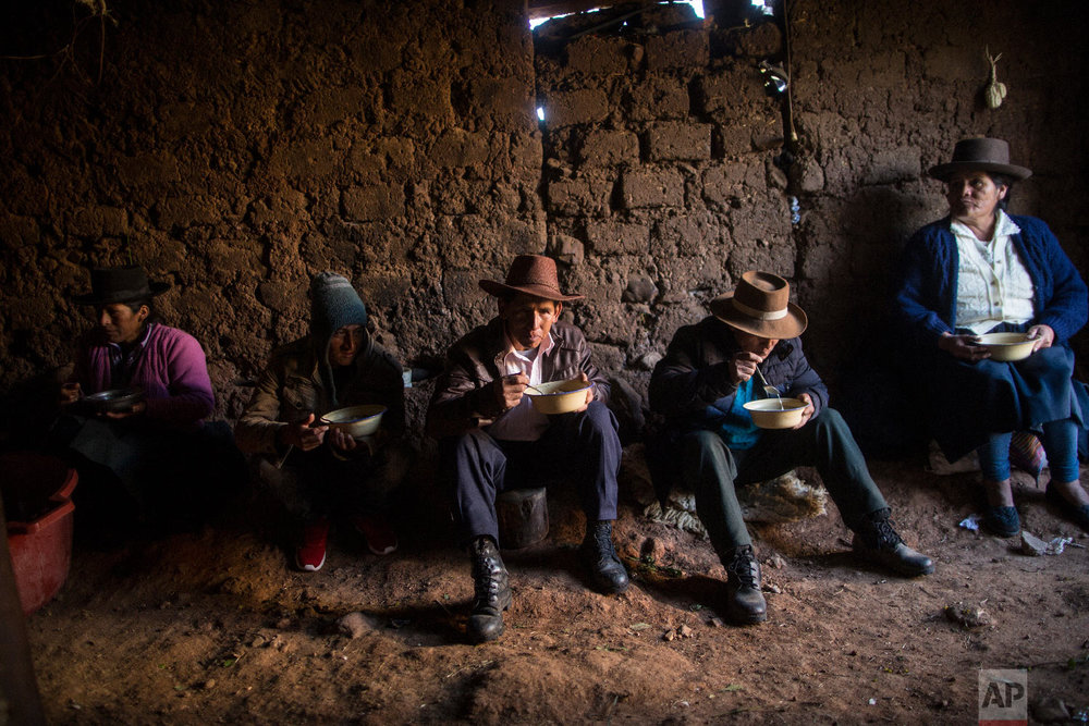 In this Aug. 15, 2018 photo, villagers eat breakfast before giving a proper burial to their loved ones who were killed by Shining Path guerrillas and the Peruvian army in the 1980s, in Quinuas, in Peru's Ayacucho province. (AP Photo/Rodrigo Abd)