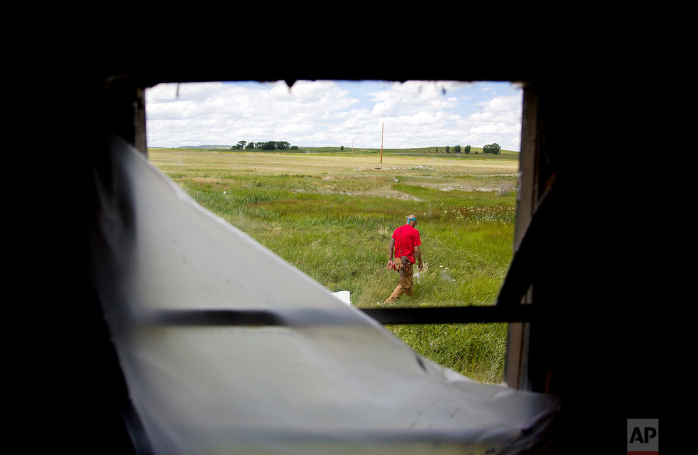 Randy Ortiz combs a field outside a trailer during a search for Ashley HeavyRunner Loring in Valier, Mont., July 11, 2018. One of Ashley's cousins lived at the trailer, and there are reports it's among the last places she was seen. (AP Photo/David Goldman)