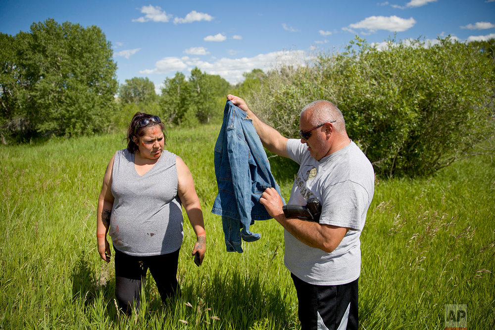 George A. Hall, right, holds up a jacket found with Lissa Loring, during a search in Valier. Mont., for Loring's cousin, Ashley HeavyRunner Loring,  July 11, 2018. (AP Photo/David Goldman)