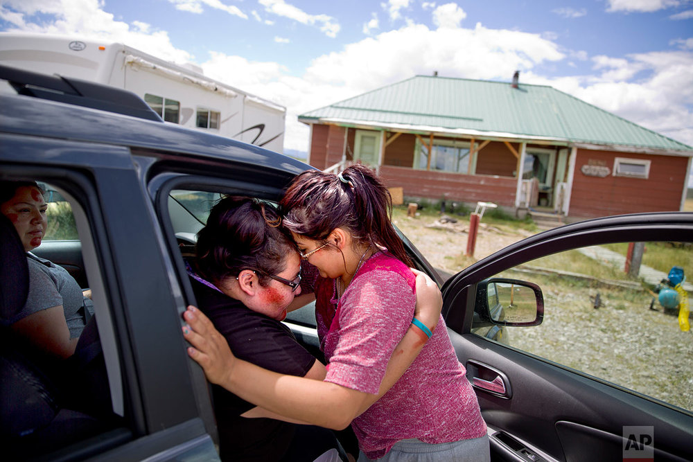 "Kimberly Loring, left, touches her forehead to her little sister, Jonnilyn, 17, as she says goodbye before heading out on a search for their missing sister, Ashley, with their cousin, Lissa Loring, on the Blackfeet Indian Reservation in Browning, Mont., July 11, 2018. ""I'm the older sister. I need to do this,"" says 24-year-old Kimberly. ""I don't want to search until I'm 80. But if I have to, I will."" (AP Photo/David Goldman)"