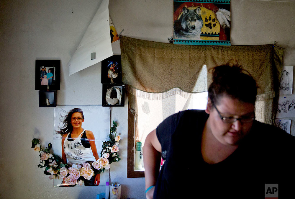 "A poster of Ashley HeavyRunner Loring hangs on the wall as her sister, Kimberly, walks through Ashley's room at their grandmother's home on the Blackfeet Indian Reservation in Browning, Mont., July 13, 2018.  ""'We have to stick together,'"" Kimberly once told her little sister while the girls were briefly in a foster home. ""I told her I would never leave her. And if she was going to go anywhere, I would find her.""(AP Photo/David Goldman)"