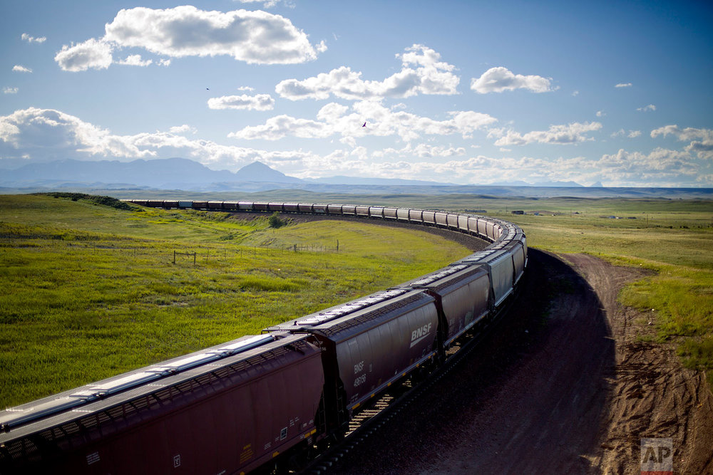 A train rounds a bend while traveling across the landscape of the Blackfeet Indian Reservation in Browning, Mont., July 10, 2018. (AP Photo/David Goldman)