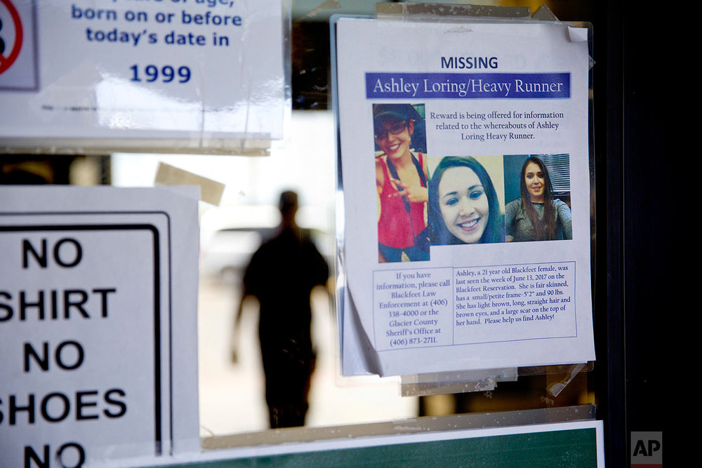 A missing poster for Ashley HeavyRunner Loring is posted to the entrance of a grocery store on the Blackfeet Indian Reservation in Browning, Mont., July 12, 2018. (AP Photo/David Goldman)