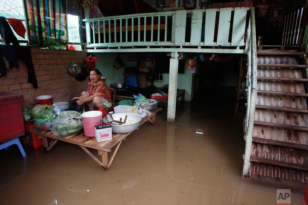 A woman works in a raised kitchen area during flood season near the Mekong River bank on the outskirts of Phnom Penh, Cambodia, Saturday, Aug. 11, 2018. (AP Photo/Heng Sinith)