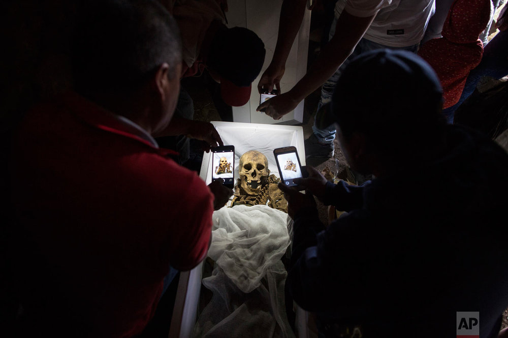 Mourners take cell phone pictures of the remains of Fortunate Ventura Huamacusi, a man who was killed by the Peruvian army in 1983, before placing the coffin in its niche at the Rosaspata cemetery in Peru's Ayacucho province on Aug. 14, 2018. Thousands of Peruvian families who have spent decades wondering about loved ones who disappeared during years of bloody conflict between the state and Maoist guerrillas have new hopes for getting the closure they have been searching for. (AP Photo/Rodrigo Abd)