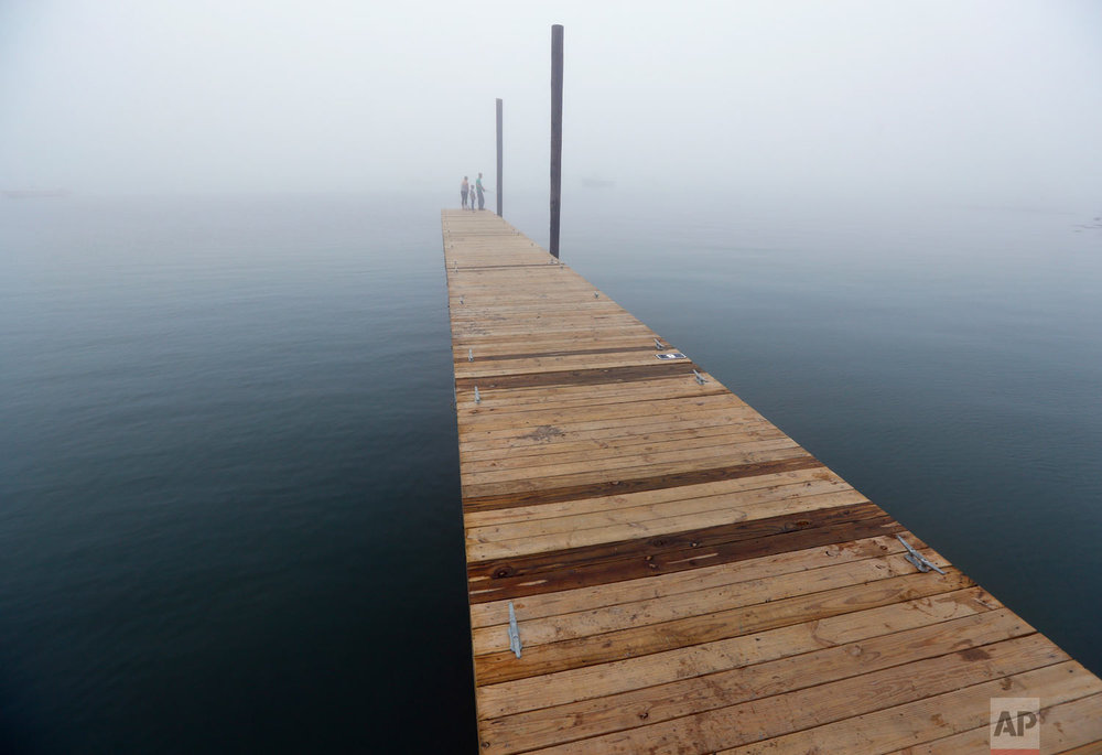A dock stretches out into a sea of fog where Matthew Harrington, his wife, Krystal, and son, Cayden, fish in Casco Bay, Tuesday, Aug. 14, 2018, in Portland, Maine. (AP Photo/Robert F. Bukaty)
