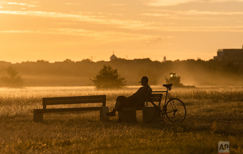 A man sits on a bench during sunset in the area of the former Tempelhof airport in Berlin, Germany, Monday, Aug. 13, 2018. (Paul Zinken/dpa via AP)