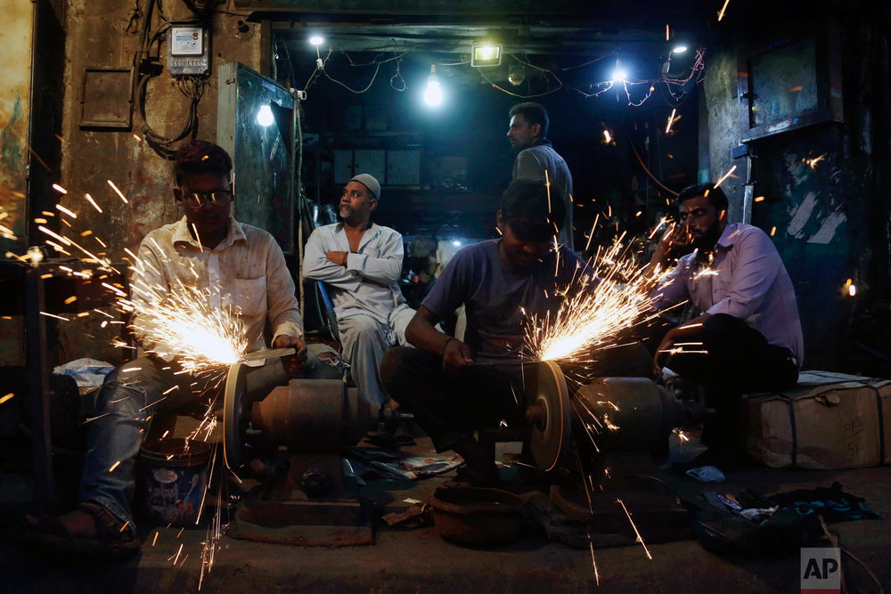 People have their knives sharpened for the upcoming Muslim festival Eid al-Adha in Karachi, Pakistan, Monday, Aug. 20, 2018. Eid al-Adha, or Feast of Sacrifice, is the most important Islamic holiday and marks the willingness of the Prophet Ibrahim (Abraham to Christians and Jews) to sacrifice his son. (AP Photo/Shakil Adil)
