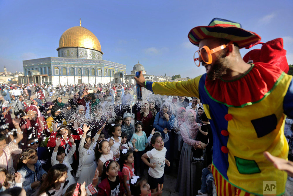 A clown sprays foam towards a group of children on the first day of Eid al-Adha near the Dome of the Rock Mosque in the Al Aqsa Mosque compound in Jerusalem's old city, Tuesday, Aug. 21, 2018. During the Eid al-Adha, or Feast of Sacrifice, Muslims slaughter sheep or cattle to distribute portions of the meat to the poor. (AP Photo/Mahmoud Illean)