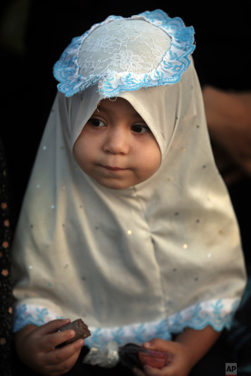 A girl joins a prayer to mark the first day of Eid al-Adha in Gaza City, Tuesday, Aug. 21, 2018. During the Eid al-Adha, or Feast of Sacrifice, Muslims slaughter sheep or cattle to distribute portions of the meat to the poor. (AP Photo/Khalil Hamra)