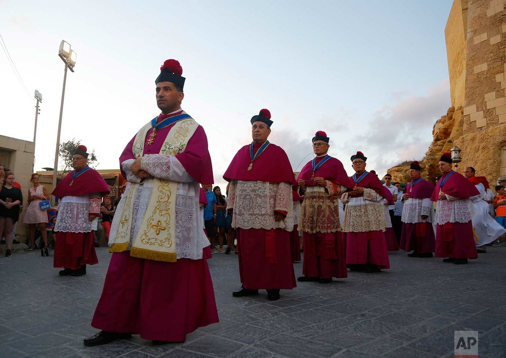 In this photo taken on Wednesday, Aug. 15, 2018, priests participate in the procession of the Virgin Mary in Rabat on the island of Gozo in the Maltese archipelago. (AP Photo/Niranjan Shrestha)