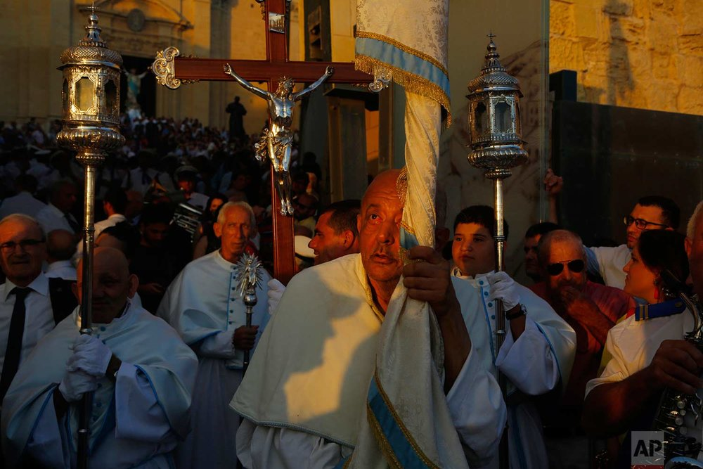 In this photo taken on Wednesday, Aug. 15, 2018, priests hold religious icons as they lead a procession during the feast day of the Assumption of Mary in Rabat on the island of Gozo in the Maltese archipelago. (AP Photo/Niranjan Shrestha)
