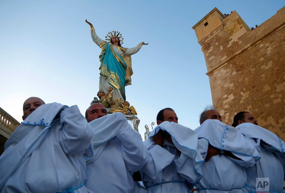 In this photo taken on Wednesday, Aug. 15, 2018, priests carry a statue of the Virgin Mary during a procession on the feast day of the Assumption of Mary in Rabat on the island of Gozo in the Maltese archipelago. (AP Photo/Niranjan Shrestha)