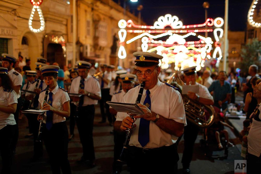 In this photo taken on Wednesday, Aug. 15, 2018, a local band club participate in a procession through the streets of Rabat on the island of Gozo in the Maltese archipelago, during the feast day of the Assumption of Mary. (AP Photo/Niranjan Shrestha)