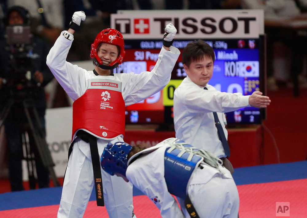 Taiwan's Poya Su, left, celebrates after winning the gold medal during their women's featherweight 53-kilogram Taekwondo match at the 18th Asian Games in Jakarta, Indonesia, Monday, Aug.20, 2018. (AP Photo/Tatan Syuflana)