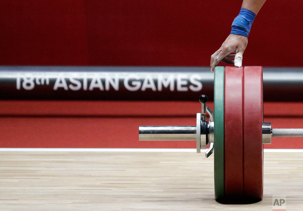 Indonesia's Wijo Bin inspects the weights on the bar as he competes in the men's 56kg weightlifting at the 18th Asian Games in Jakarta, Indonesia on Monday, Aug. 20, 2018. (AP Photo/Aaron Favila)