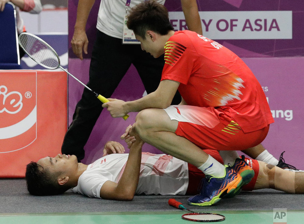 China's Yuqi Shi, right, comes over to Indonesia's Anthony Ginting, left, after he retired and cannot continue due to injury during their men's team badminton finals at the 18th Asian Games in Jakarta, Indonesia, Wednesday, Aug. 22, 2018. (AP Photo/Aaron Favila)