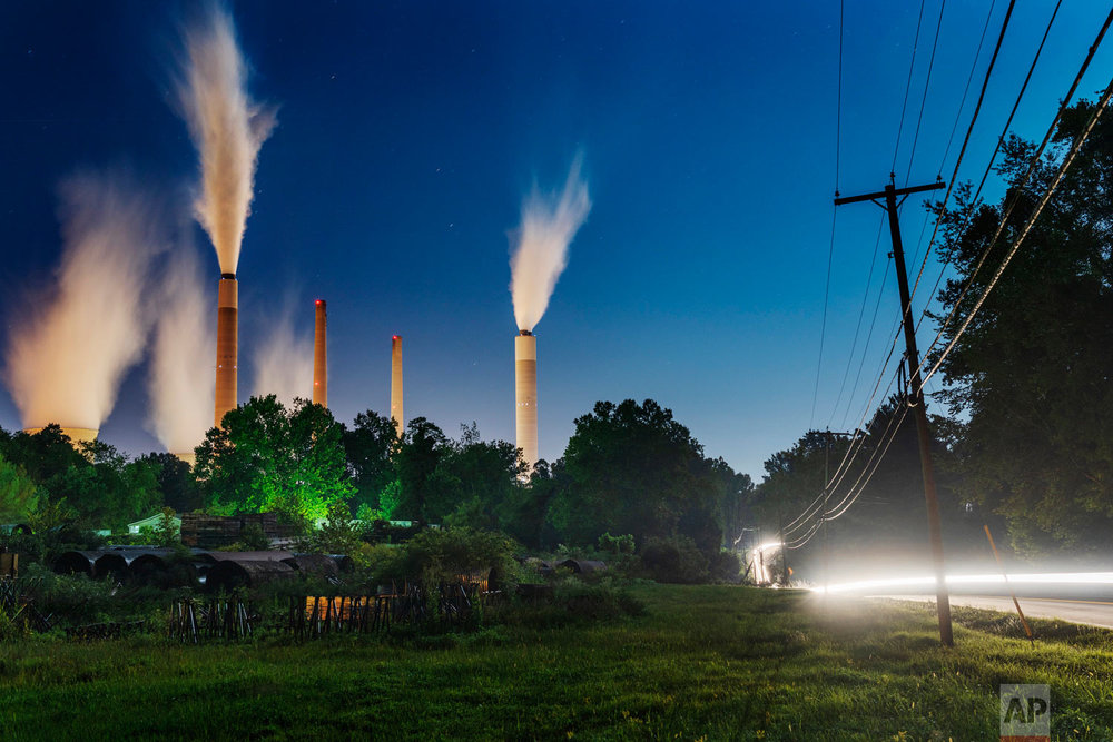 The John E. Amos Power Plant is seen from a field outside of Winfield, W. Va., on Thursday night, Aug. 23, 2018. Built in the 1970's, the coal-fired facility is the largest in the American Electric Power company's portfolio. Many of AEP's smaller coal-fired power plants in Appalachia closed in response to environmental regulations such as the Clean Power Plan in 2015. (Craig Hudson/Charleston Gazette-Mail via AP)