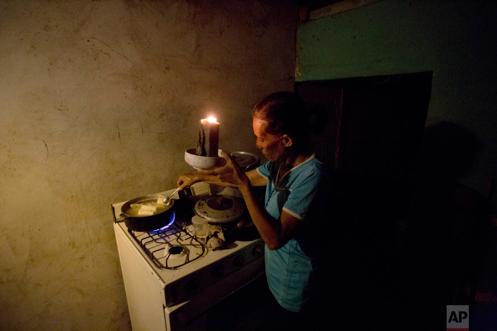 Mireya Marquez uses candlelight to cook her dinner of boiled cassava, also known as yuca and manioc, during a blackout in Maracaibo, Venezuela on Sunday, Aug. 19, 2018. For months, Maracaibo's residents have endured rolling blackouts, but things turned dire on August 10 when a fire destroyed a main power line supplying the city of 1.5 million people. (AP Photo/Fernando Llano)
