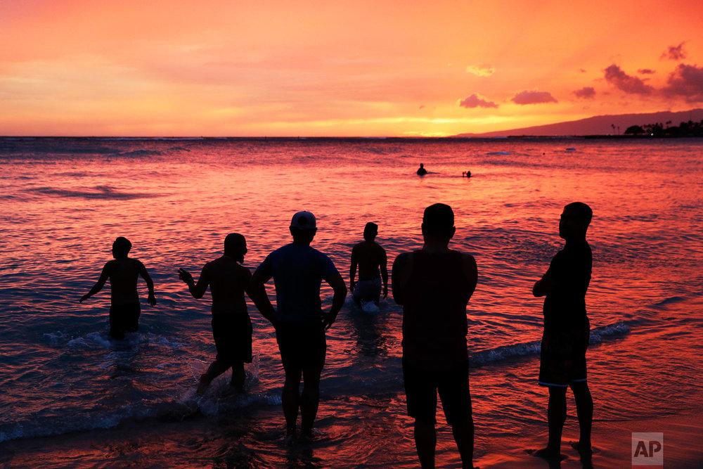 People watch the sunset on Waikiki Beach ahead of Hurricane Lane, Thursday, Aug. 23, 2018, in Honolulu. (AP Photo/John Locher)