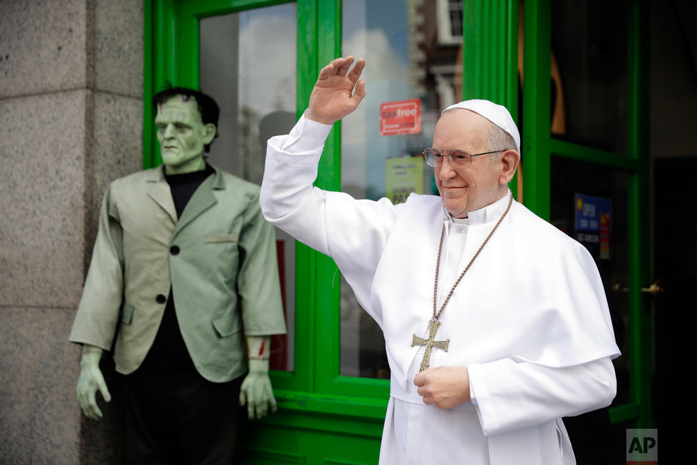A recently unveiled waxwork statue of Pope Francis is displayed next to a Frankenstein figure outside the National Wax Museum in Dublin, Ireland, Friday, Aug. 24, 2018. Pope Francis arrives on Saturday for a two-day visit to Ireland. (AP Photo/Matt Dunham)