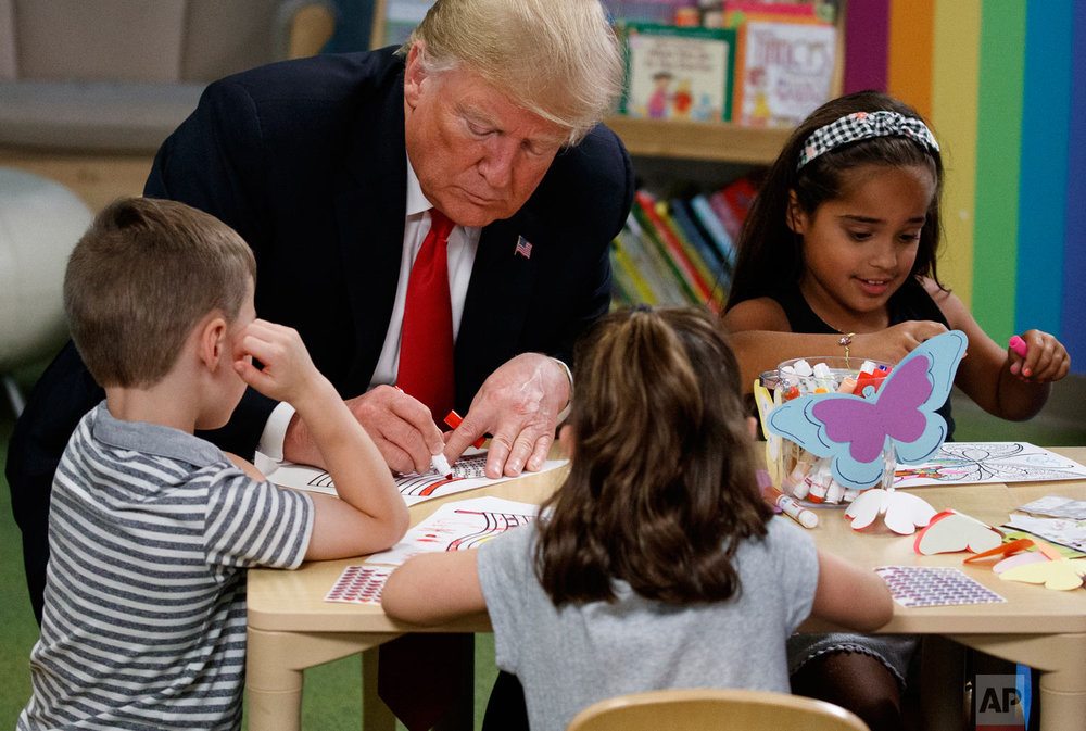President Donald Trump writes in a coloring book during a visit with a group of children at the Nationwide Children's Hospital, Friday, Aug. 24, 2018, in Columbus, Ohio. (AP Photo/Evan Vucci)