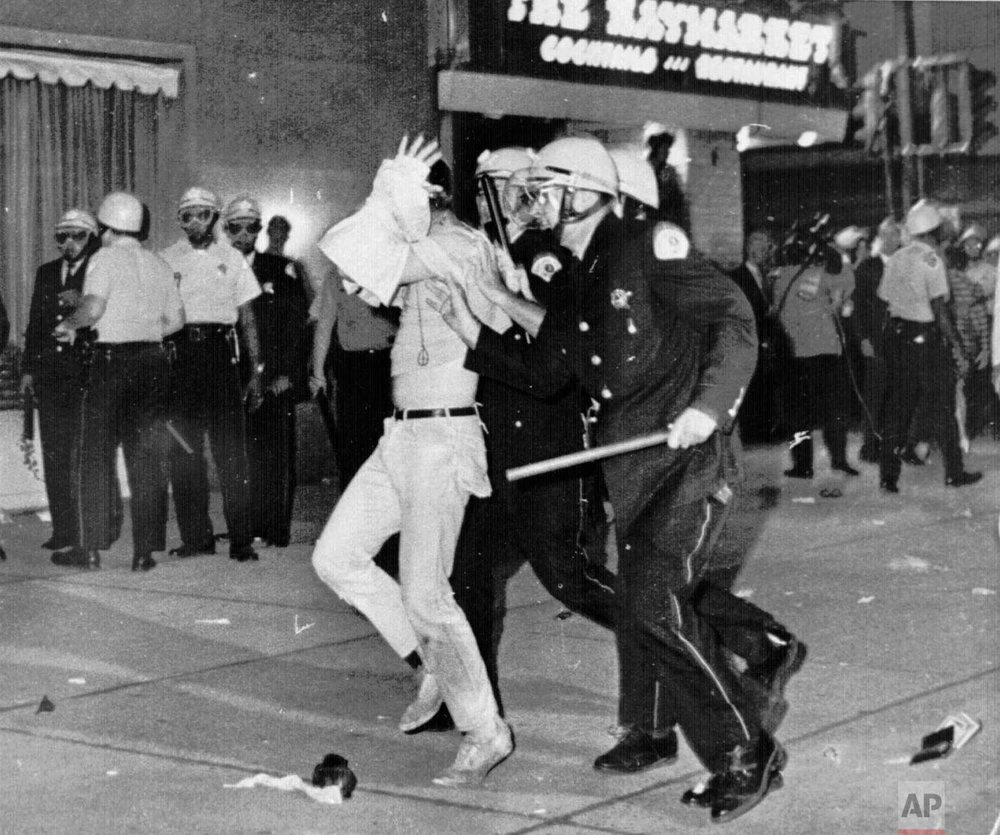 A demonstrator with his hands on his head is led by Chicago Police down Michigan Avenue the night of Aug. 28, 1968 during a confrontation with police and National Guardsmen who battled demonstrators near Conrad Hilton Hotel, headquarters for the Democratic National Convention. (AP Photo)