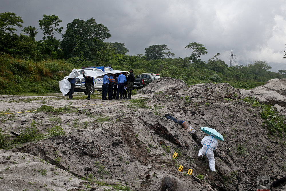 Police investigators use a body bag to keep dry in the rain, as a colleague recovers a body in an area where people dig for sand used in construction, in San Pedro Sula, Honduras, July 11, 2018. Investigators said the victim had been there various days, was a male between 18 and 23 years old, and showed execution-style injuries. (AP Photo/Esteban Felix)