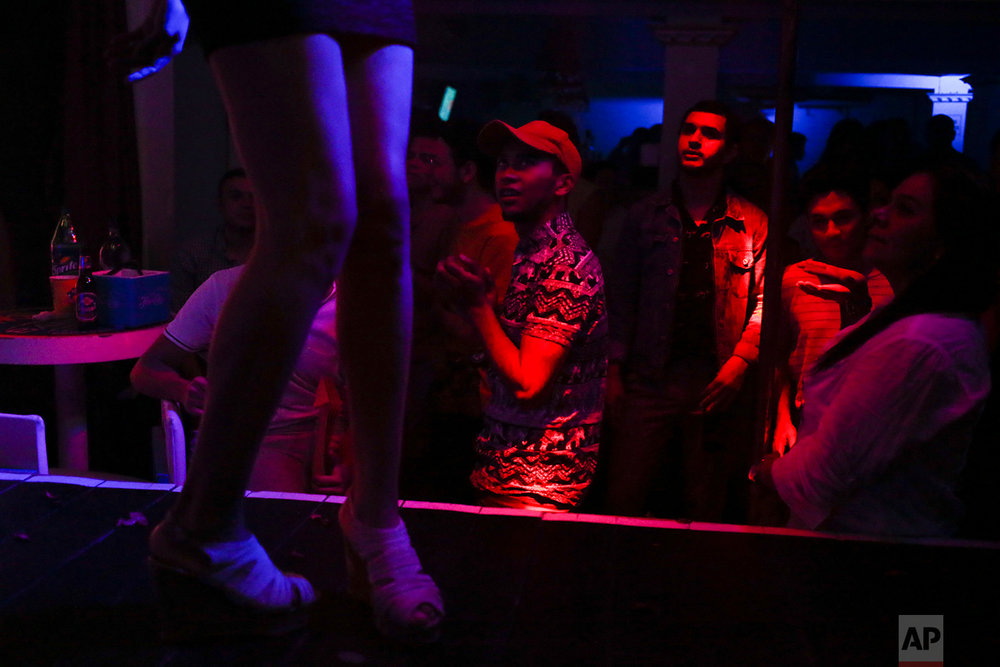"In this July 26, 2018 photo, people watch the gay beauty contest coined ""Our Beauty"" at a disco club in Tegucigalpa, Honduras. LGBTI organizations in Honduras have denounced at least 40 murders of their community since the start of 2017, with most being victims of gunfire. (AP Photo/Esteban Felix)"