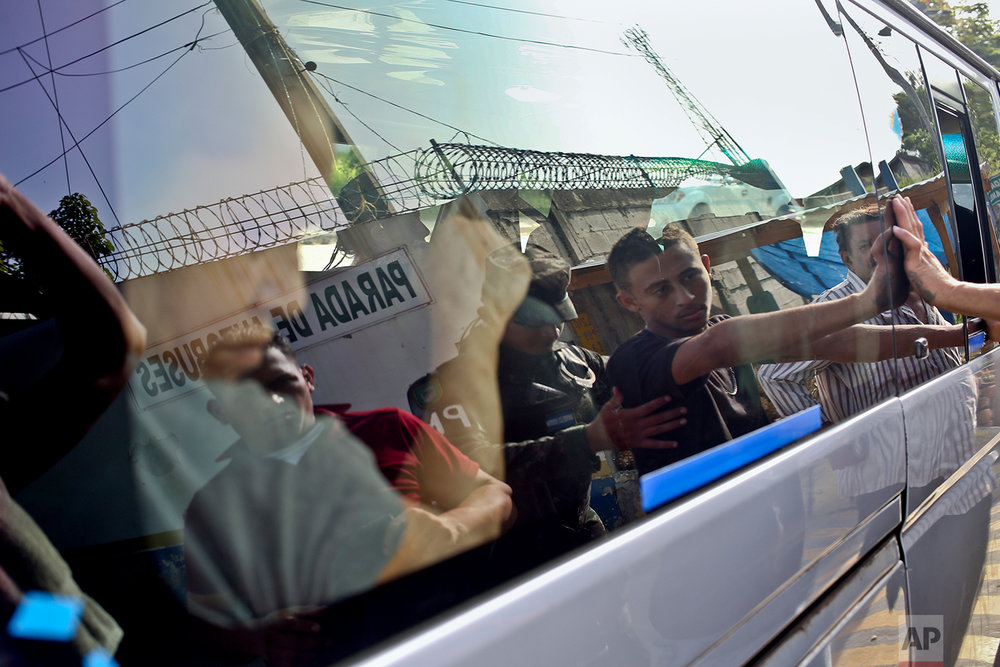 In this July 4, 2018 photo, military police frisk and search passengers traveling on public bus, at the entrance to the Rivera Hernandez neighborhood, a high crime area of San Pedro Sula, Honduras. Military police regularly stop residents in private or public transportation, usually men, to search them for weapons or signs that they belong to a gang. The men frisked in this instance were let go. (AP Photo/Esteban Felix)