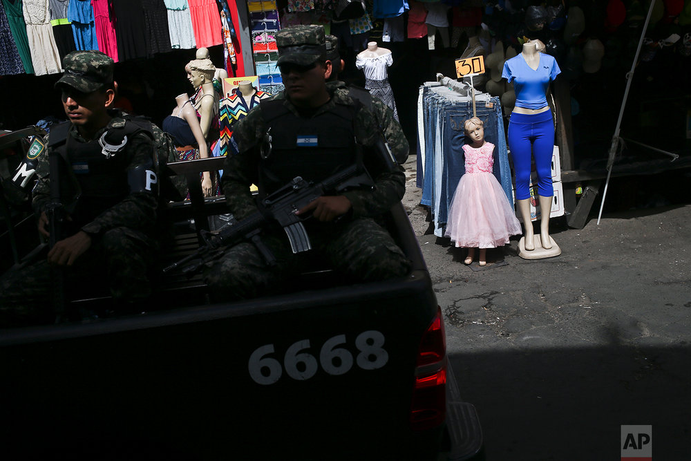 In this July 24, 2018 photo, military police patrol past the Comayaguela  market in Tegucigalpa, Honduras. The market is the capital's biggest, serving as the city's outlet  as well as one of the highest crime rate areas, so police can be seen patrolling 24-7.  (AP Photo/Esteban Felix)