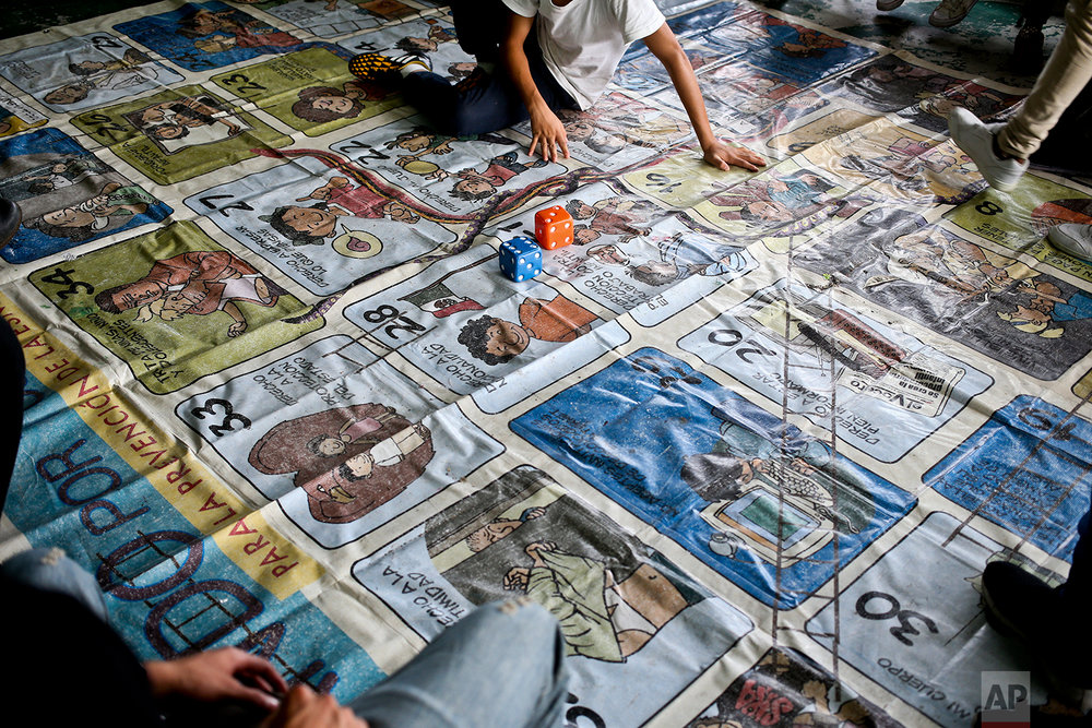 In this Aug. 1, 2018 photo, a mat with cartoon images explaining different human rights covers the floor at a shelter that takes in deported migrant youths who cannot return home due to high violence in their communities, where they risk getting forced into gangs, in Tegucigalpa, Honduras. Youths roll the oversized dice to obtain a number, which points to one of the diagrams. They then read out loud what the square says, which starts a discussion on the diagram's particular human right's issue.  (AP Photo/Esteban Felix)