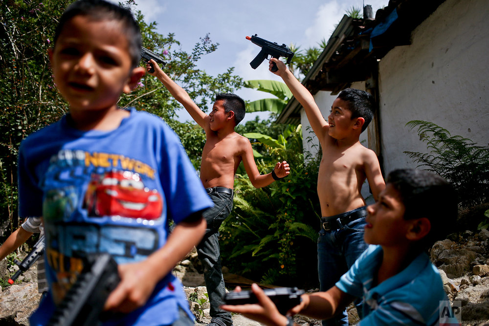 "In this July 22, 2018 photo, brothers and cousins pretend to shoot little girls watching them from a window, as they play cops and gangsters with toy guns that were a gift from an uncle, in Taulabe, Honduras. When asked if they were cops or gangsters, they paused to think about it and answered ""cops."" (AP Photo/Esteban Felix)"