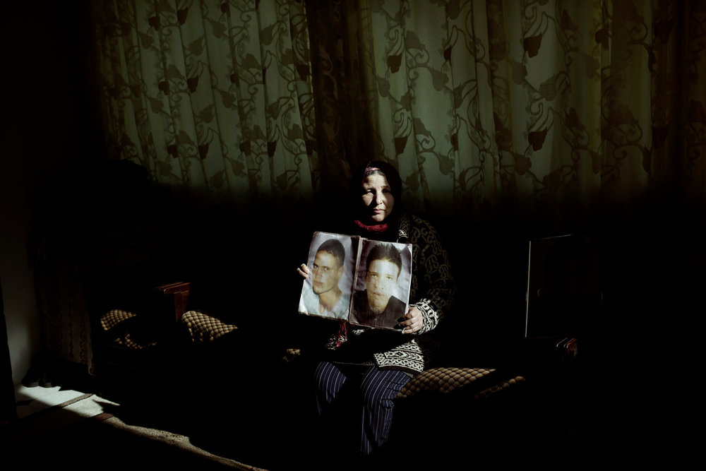 In this Thursday, April 12, 2018 photo, Fathia Jejli holds a photo of her son, Hossam Edin Jejli, right, and her nephew, Hamed Ben Brayek, who went missing in 2011, at her home in the town of Ras Jebel, Tunisia. (AP Photo/Nariman El-Mofty)