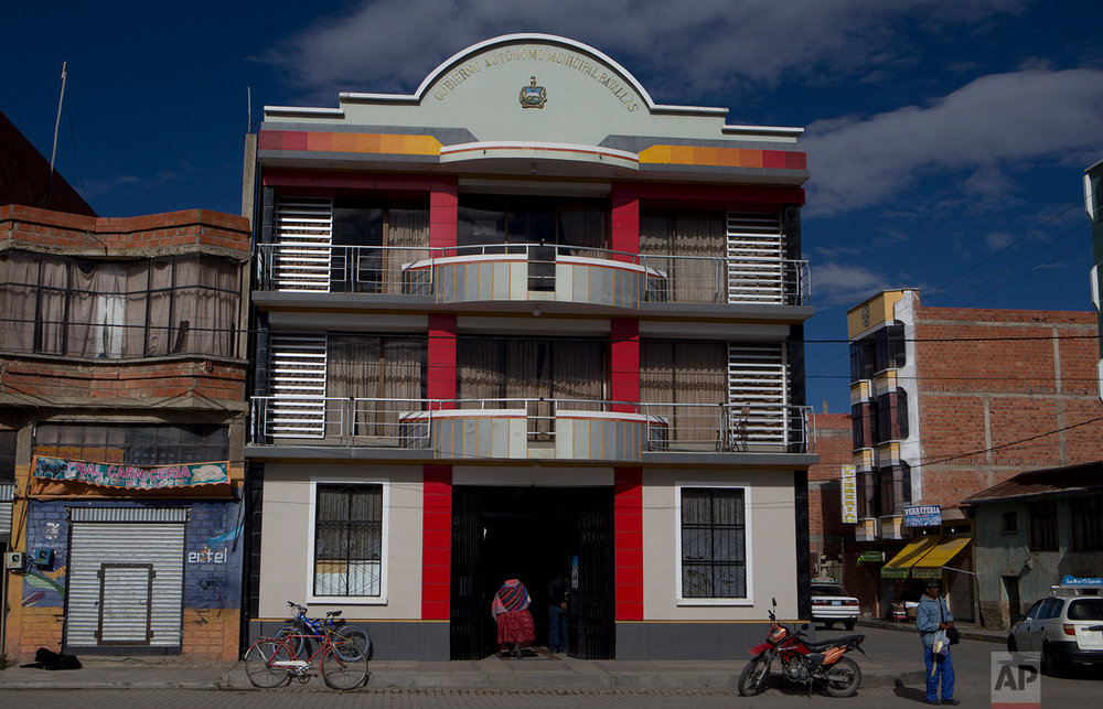In this July 25, 2018 photo, an Aymara woman enters to the municipal mayor's office in Batallas, Bolivia. In some elections, men are required to run with a female alternate, and vice versa. If a woman holds an elected office sometimes her male alternate will seek to oust her to take power.(AP Photo/Juan Karita)