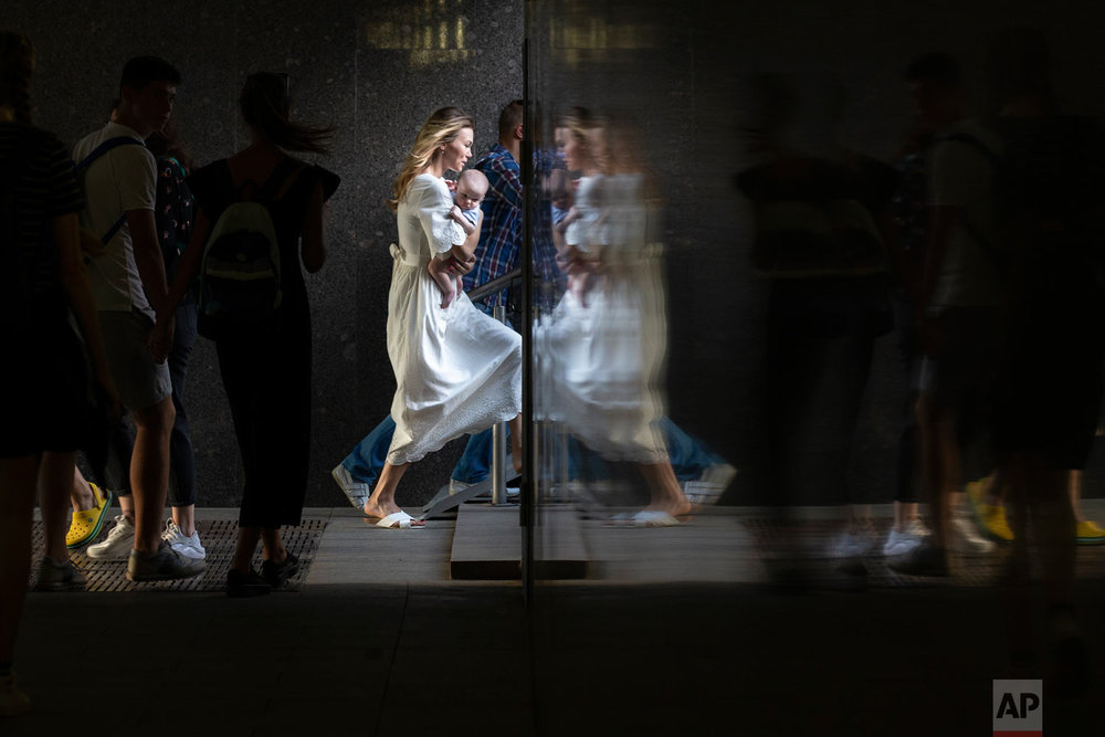 A woman carrying a child is reflected in a wall as she walks through the subway system in Moscow, Russia, Wednesday, Aug. 29, 2018. (AP Photo/Alexander Zemlianichenko)