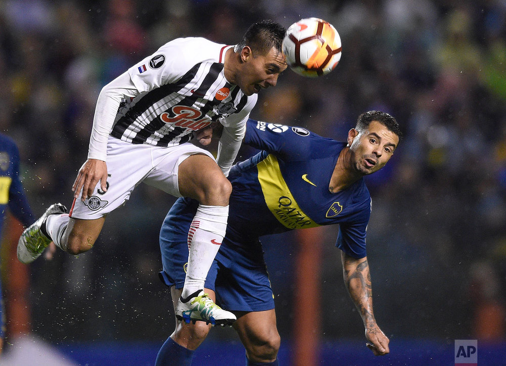 Angel Lucena of Paraguay's Libertad, left, heads the ball alongside Edwin Cardona Argentina's Boca Juniors during a Copa Libertadores soccer match in Buenos Aires, Argentina, Aug. 8, 2018. (AP Photo/Gustavo Garello)