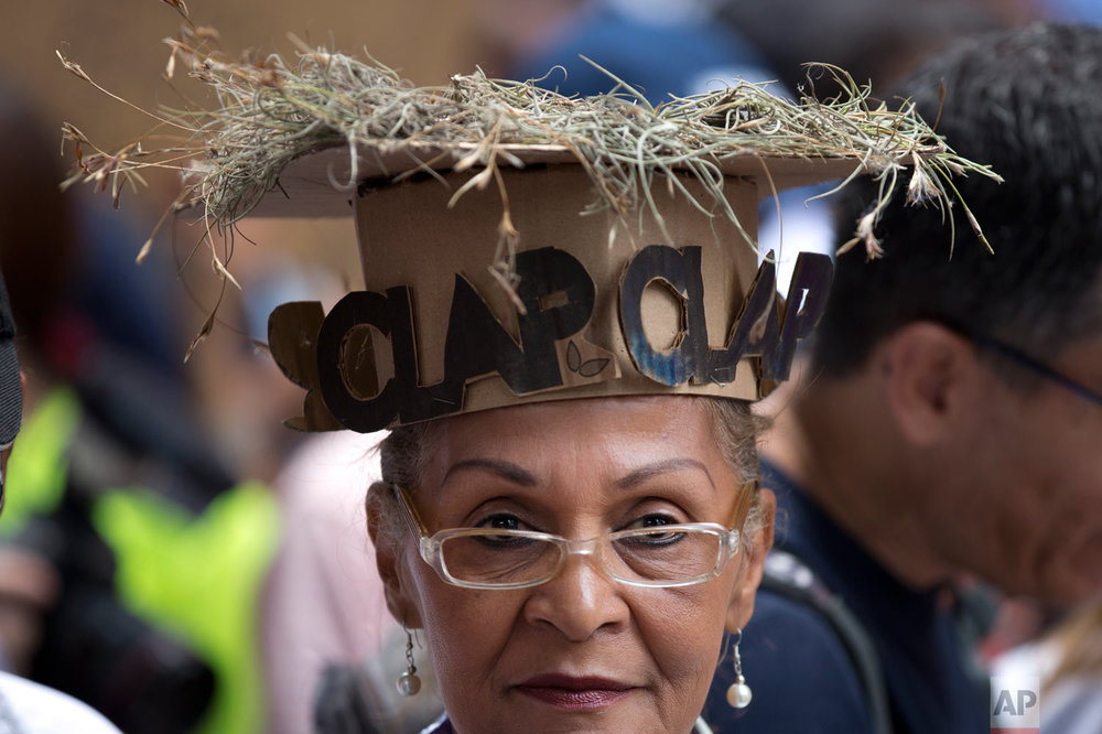 """A woman wears a cardboard hat with dry grass on top and letters in Spanish that read """"CLAP,"""" referring to government subsidized food through the """"CLAP"""" program, which stands for Local Committees of Supply and Production, during a protests against the government of President Nicolas Maduro in Caracas, Venezuela, Aug. 16, 2018. (AP Photo/Ariana Cubillos)"""