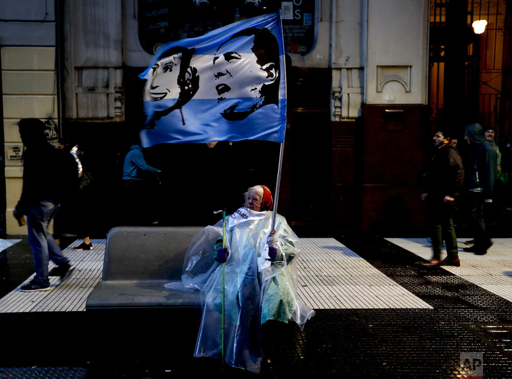 A demonstrator holds an Argentine flag of Argentina's late President Juan Domingo Peron and first lady Evita near Plaza de Mayo, during a protest in Buenos Aires, Argentina, Aug. 30, 2018. People  are demonstrating in support of public university education, demanding raises for teachers and more investment in higher level, public education. (AP Photo/Natacha Pisarenko)