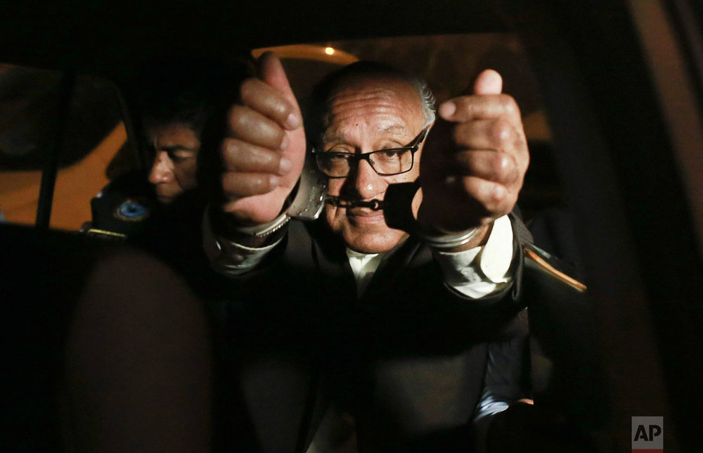 Judge Juan Gonzales shows his handcuffs to the press after he was detained by anti-corruption police in Lima, Peru, Aug. 20, 2018. Gonzalez was detained after allegedly receiving a little more than the equivalent of 1,000 dollars to rule in favor of a group of criminals. (Renzo Salazar/Peru 21 via AP)